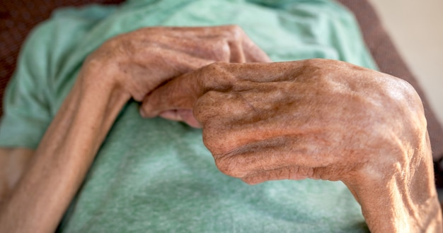 La main du patient âgé est pliée.