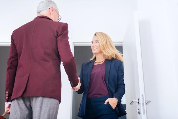Main du patron. élégante femme d'affaires élégante portant un joli collier serrant la main avec son patron après une réunion importante