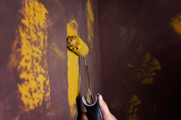 La main du peintre en bâtiment est peinte en jaune sur le vieux mur marron avec copie espace.