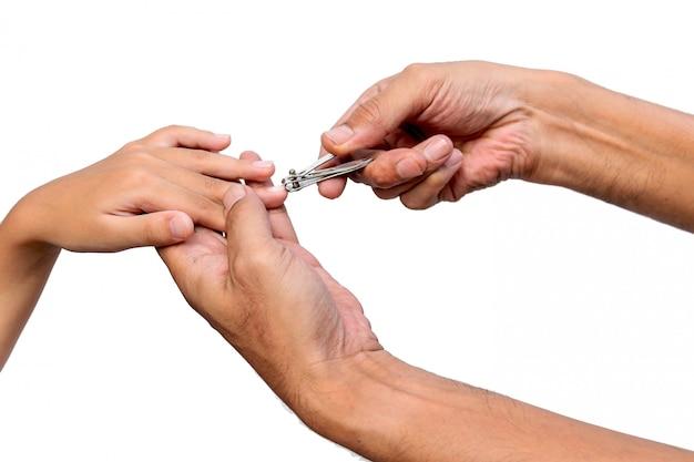 La main du père closeup utilise des coupe-ongles en acier inoxydable pour couper l'ongle du fils sur un fond blanc.