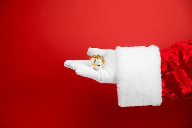 Main du père noël avec petite boîte cadeau blanche sur rouge