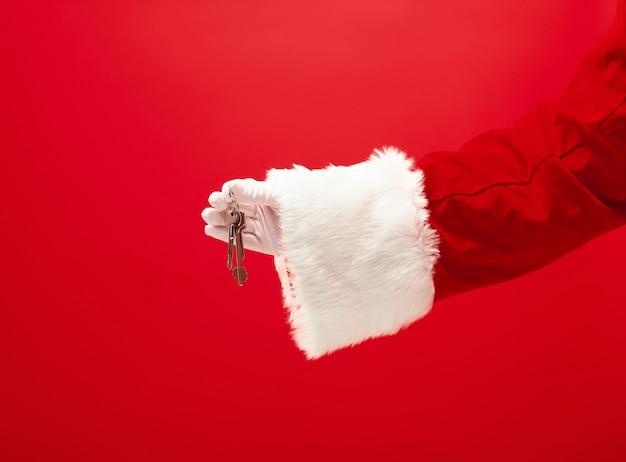 La main du père noël tenant un appartement ou des clés de voiture comme cadeau sur le rouge