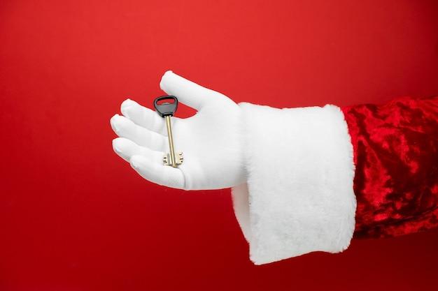 La main du père noël tient la clé de la maison.