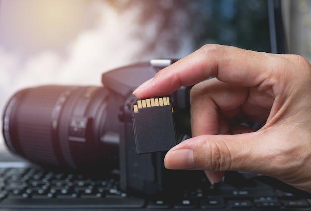 Main du photographe tenant la carte mémoire pour préparer son appareil photo avant la photographie.