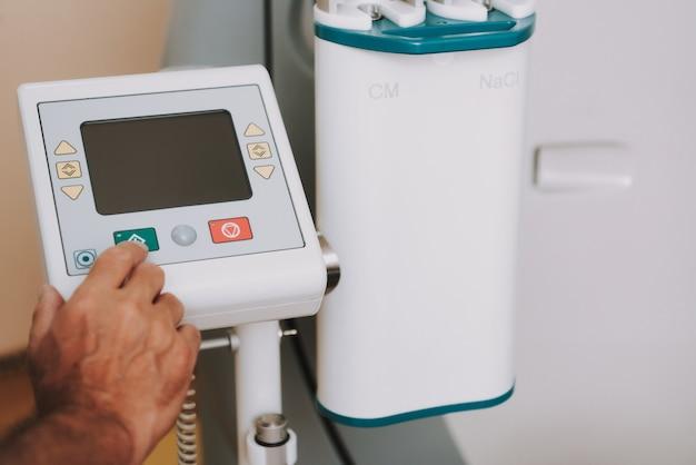Main du radiologue lors du lancement d'un scanner ou d'un scanner irm