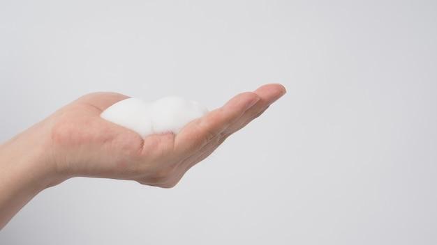 Main avec du savon moussant pour les mains et des bulles pour laver et rincer sur fond blanc.