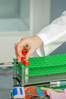 La main du technicien met des tests de tube de sang vide à un support dans le laboratoire