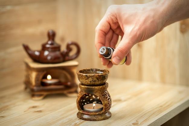 La main du thérapeute verse des gouttes d'huile essentielle au diffuseur en céramique dans le salon spa