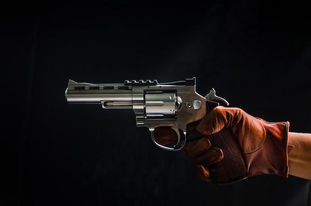 La main du tireur avec un coup de feu, avec un fond noir.