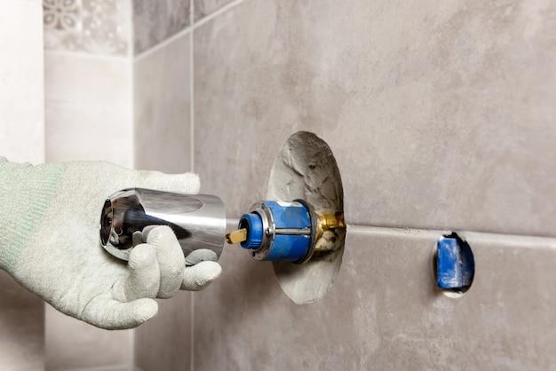 La main du travailleur monte un robinet intégré