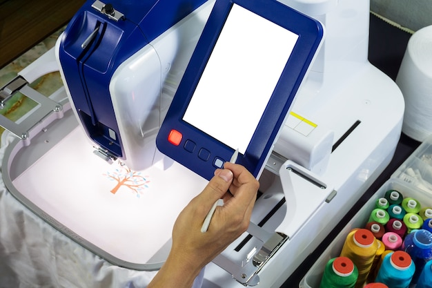 La main du travailleur tient un bâton travaillant avec des machines à broder