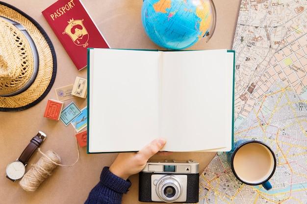 Main du voyageur tenant un livre clair
