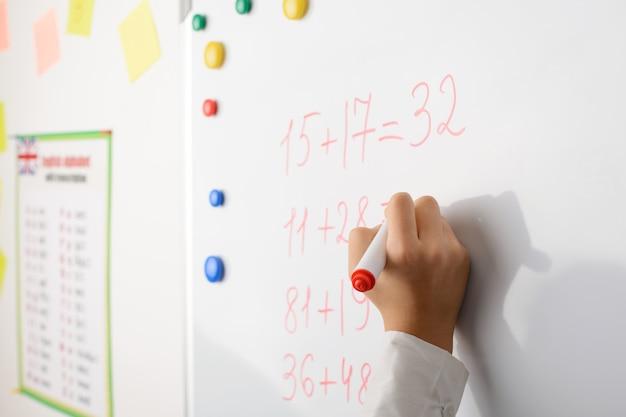 Main d'une écolière apprenant à compter des nombres au tableau noir