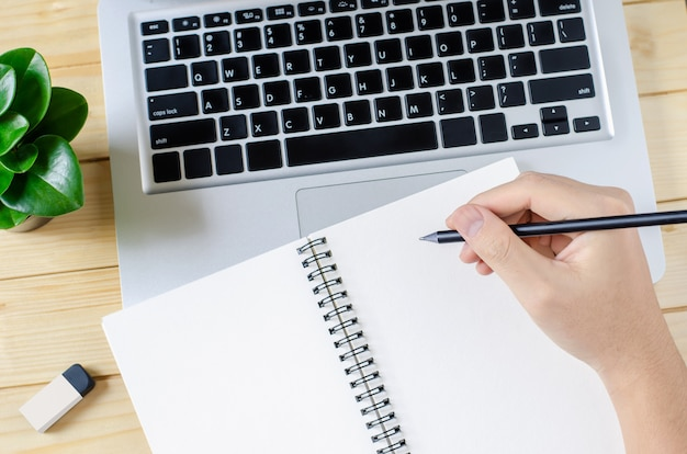 Main écrire sur le carnet de croquis blanc vierge
