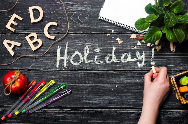 La main écrit des vacances sur un tableau noir de planches de bois