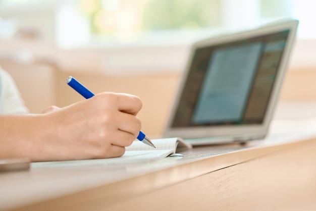 La main de l'élève garde un stylo et écrit dans un cahier.