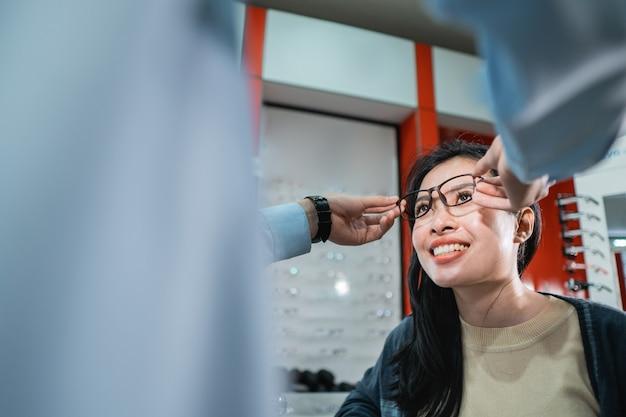 La main d'un employé aide à mettre une paire de lunettes qu'une femme qui a fait un examen de la vue a choisie dans une clinique ophtalmologique