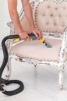 Une main d'employé de teinturier nettoie un canapé classique avec une méthode d'extraction professionnelle.