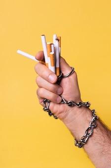 Main enchaînée tenant des cigarettes