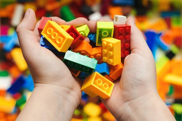 La main de l'enfant avec des blocs en plastique colorés