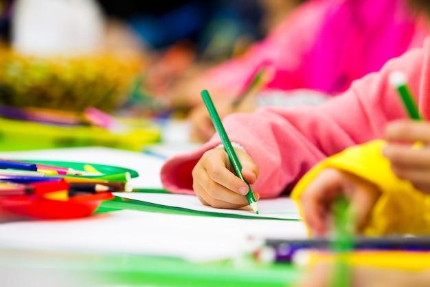 Main d'un enfant dessinant un crayon sur papier, une partie du corps