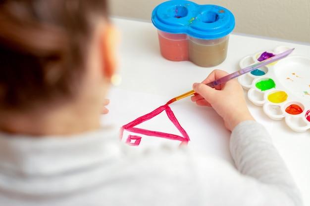 Main d'enfant dessinant la maison.