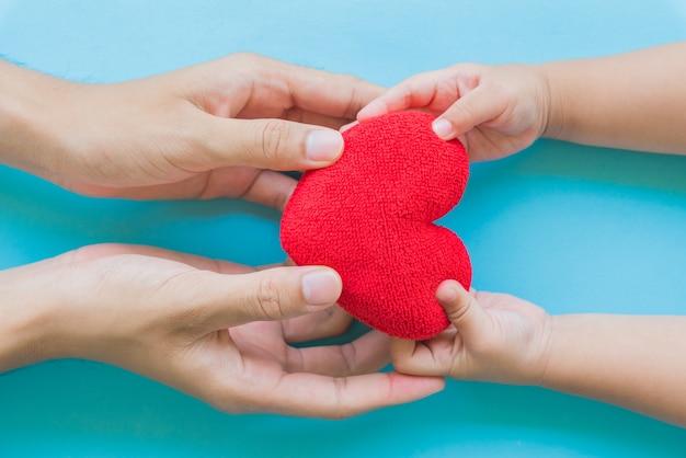 Main d'enfant donnant un coeur rouge à son père, concept d'amour et de soins de santé.
