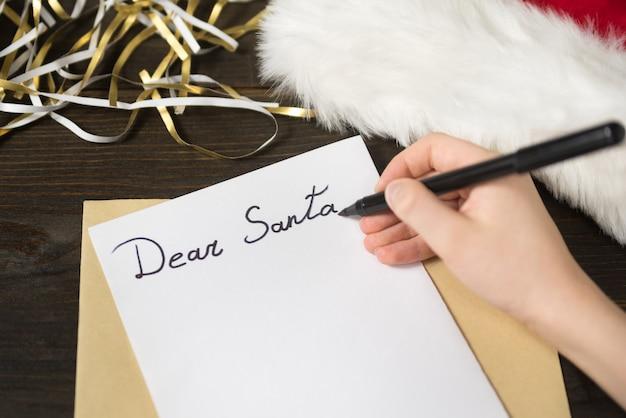 La main de l'enfant écrit une lettre au père noël