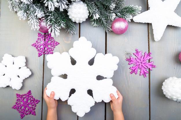 Main d'enfant avec un flocon de neige de noël décoratif
