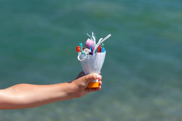 La main de l'enfant sur fond de mer contient des ordures en plastique collectées sur la plage
