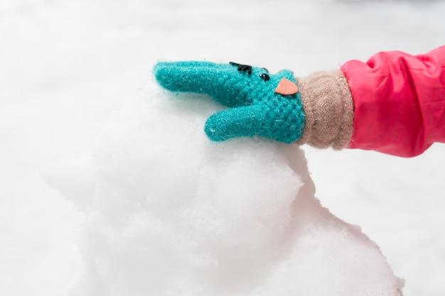 Main d'enfant avec gant d'hiver moulage bonhomme de neige dans la terre de neige avec plaisir