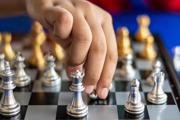 Main d'enfant jouant aux échecs
