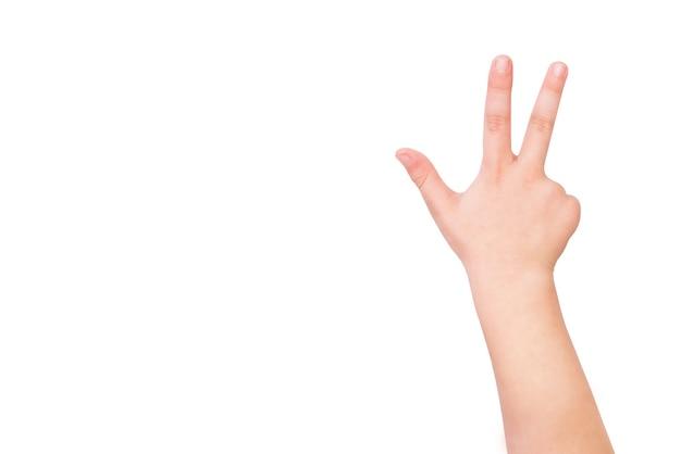 La main de l'enfant montre trois doigts sur un fond blanc