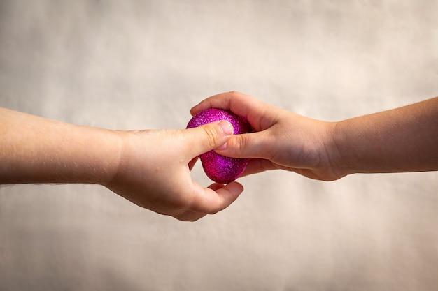 La main d'un enfant passe un cœur écarlate à la main d'un autre enfant.
