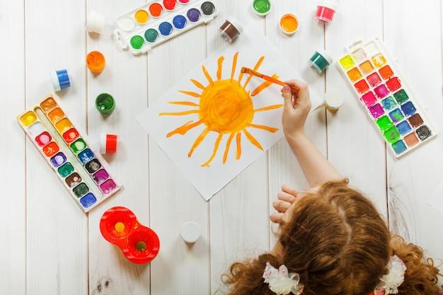 Main d'enfant avec des pinceaux, dessin sur papier blanc jaune soleil.