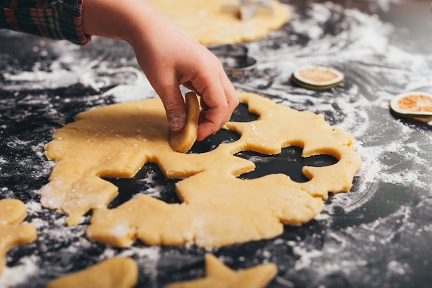 La main de l'enfant prend un morceau de pain d'épice qu'elle a fait.