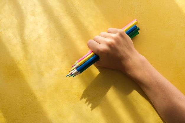 Une main d'enfant ramasser des crayons de couleur sur fond jaune