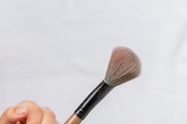 Main de l'enfant tenant des pinceaux de maquillage à rio de janeiro.