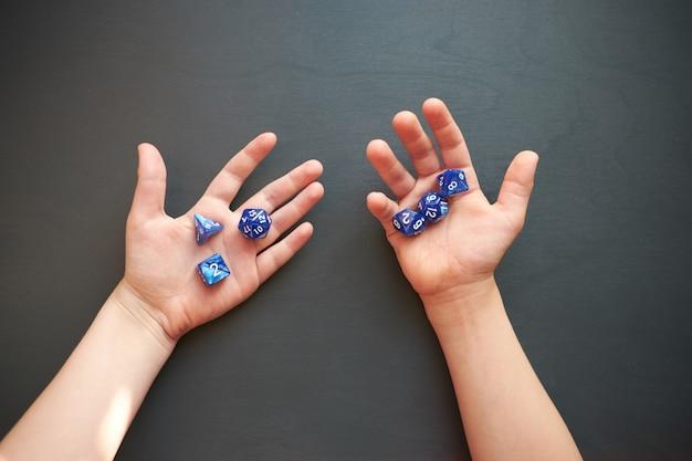 Main d'enfant tenant des dés pour un jeu de rôle sur une surface grise
