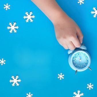 La main de l'enfant tenant un réveil bleu montrant cinq à douze avec des flocons de neige en papier