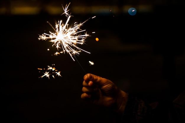 La main de l'enfant tenant un sparkler qui grésille et brille pendant la nuit.