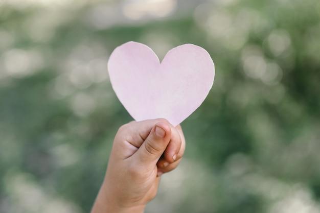 La main de l'enfant tient un cœur.