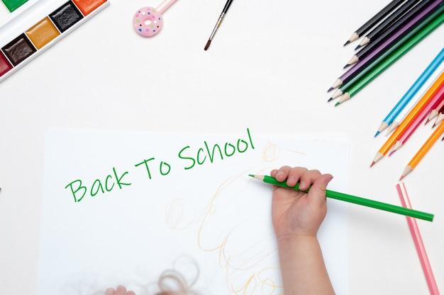Main de l'enfant tient un crayon, inscription de retour à l'école