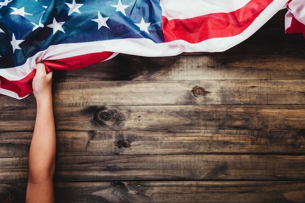 La main d'un enfant tient le drapeau des états-unis d'amérique