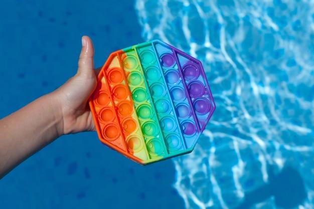 La main de l'enfant tient le jouet pop-it anti-stress coloré en silicone populaire au-dessus de l'eau dans la piscine