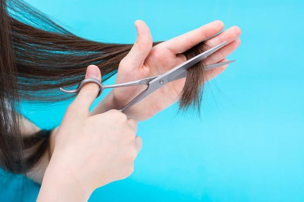 La main des enfants coupe les extrémités des cheveux sur un fond bleu.