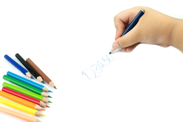 Main d'enfants avec un crayon écrivant des mots anglais à la main sur du papier bloc-notes blanc