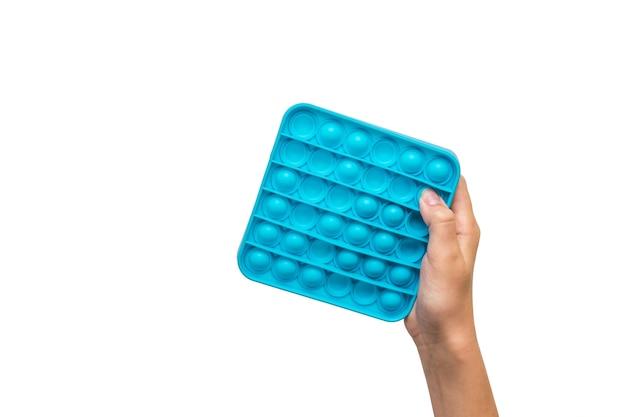 La main des enfants avec un jouet en silicone pop it isolé sur une surface blanche. un produit anti-stress populaire.