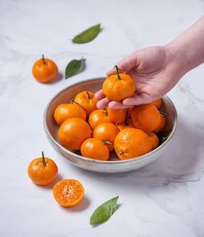 La main des enfants prend la mandarine douce du bol en céramique sur une table en marbre blanc. image verticale