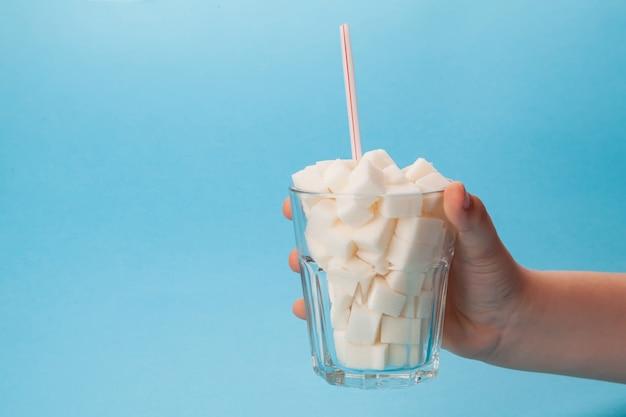 La main des enfants tient un verre en verre avec un tube plein de morceaux de sucre